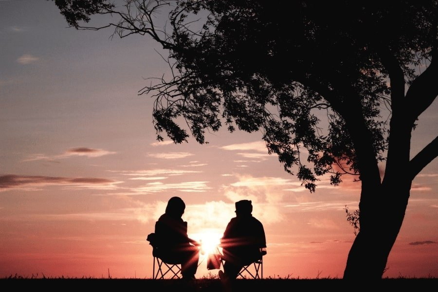 mom and dad sitting on a camping chair next to a true watching the sunset